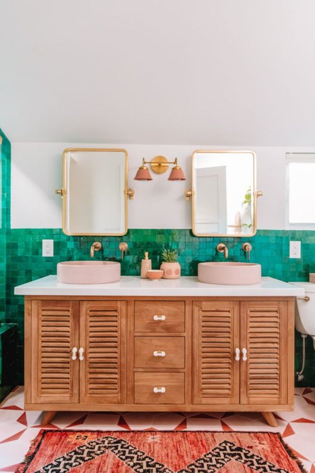 green tiled bohemian bathroom lighting idea with wooden vanity and pink wall lights