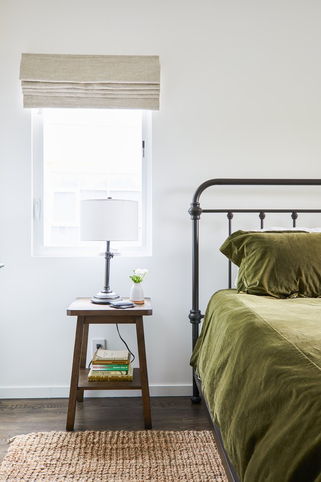 Bedroom with green bedding and rusic nightstand