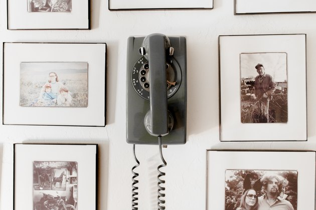 Personal photographs surround a vintage rotary phone.
