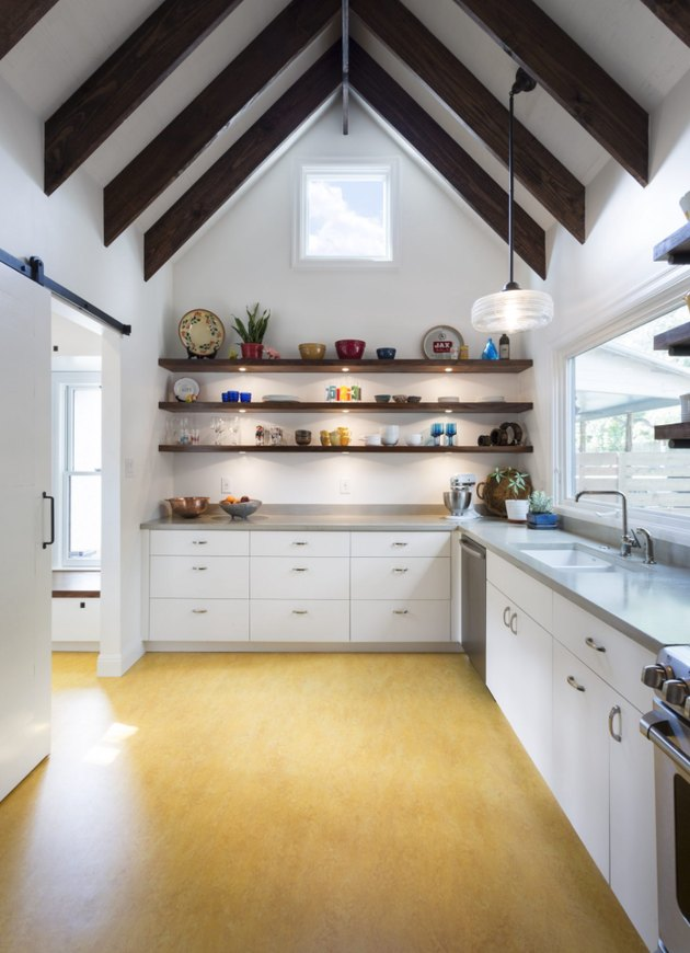 yellow linoleum kitchen flooring with open shelving and exposed ceiling beams