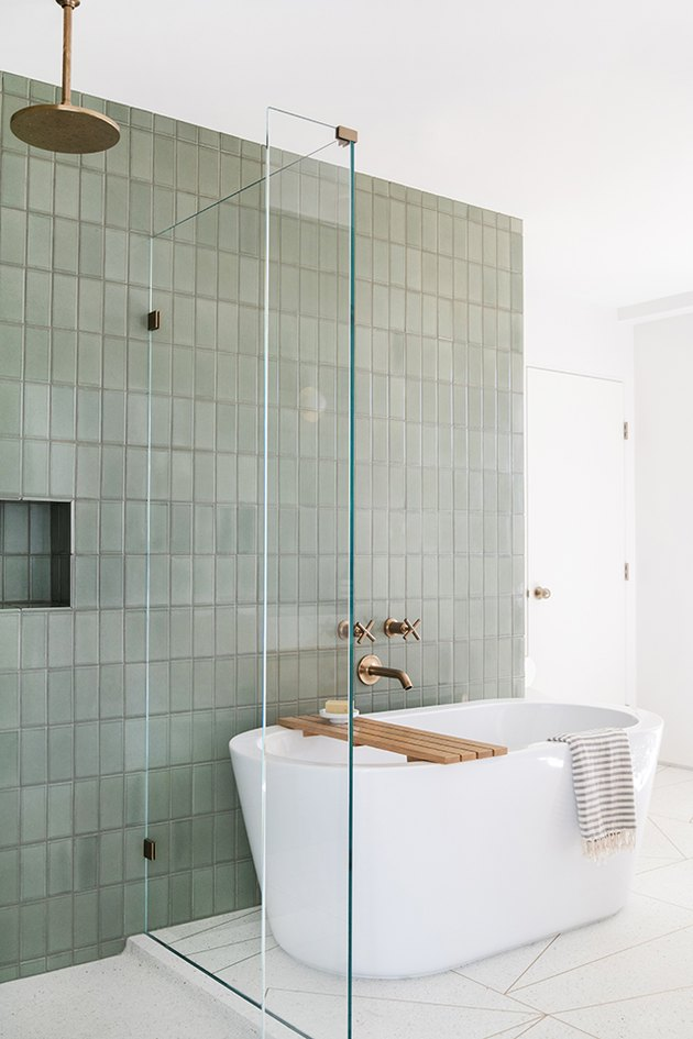 Modern bathroom with freestanding bathtubs next to green wall tile
