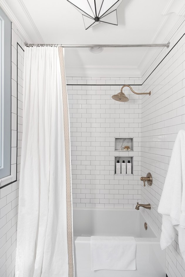 Modern bathroom with alcove bathtubs surrounded by subway tile