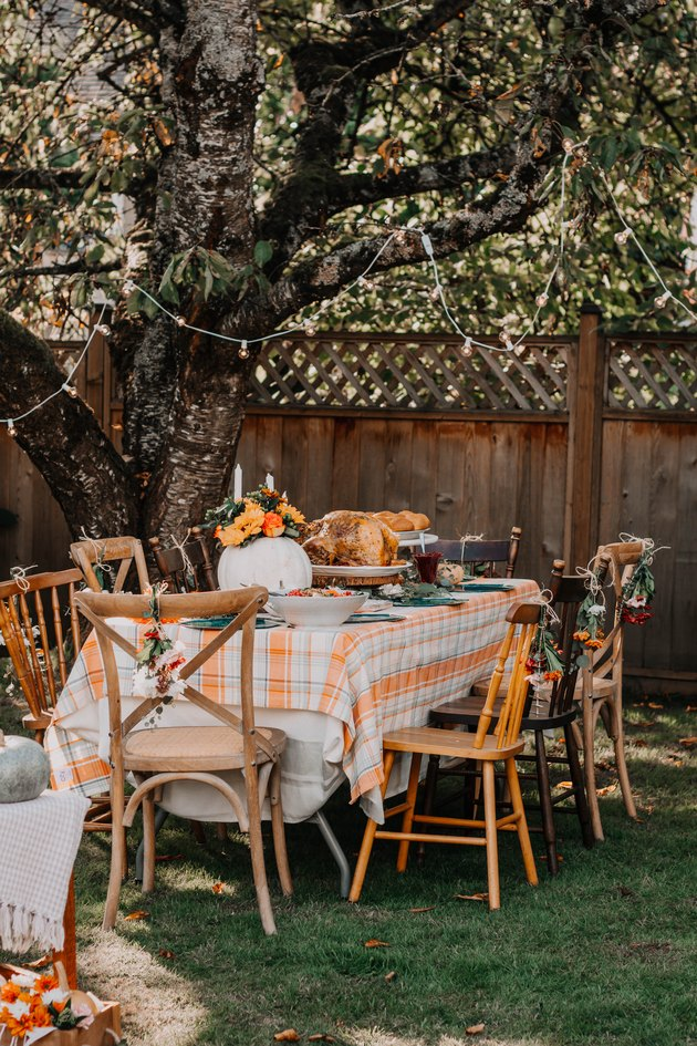 outdoor fall party idea with plaid tablecloth and string lights