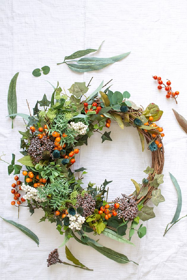fall wreath made with foraged greens, berries, and dried flowers