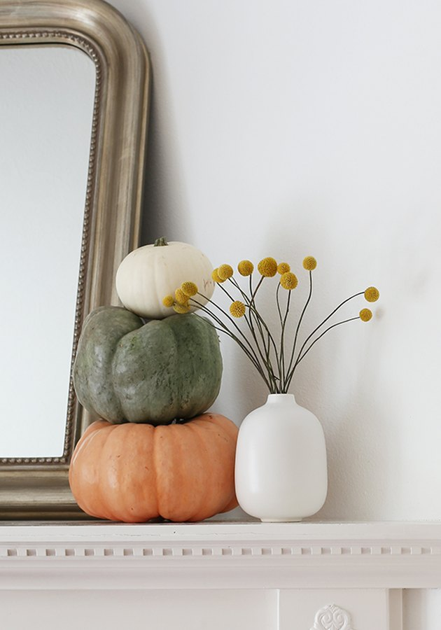 Fall decor idea with three stacked pumpkins and dried yellow flowers in white vase