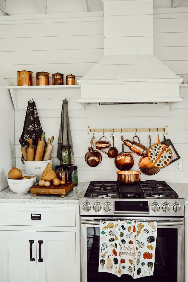 fall kitchen decor in white kitchen with copper pots hanging above the stove