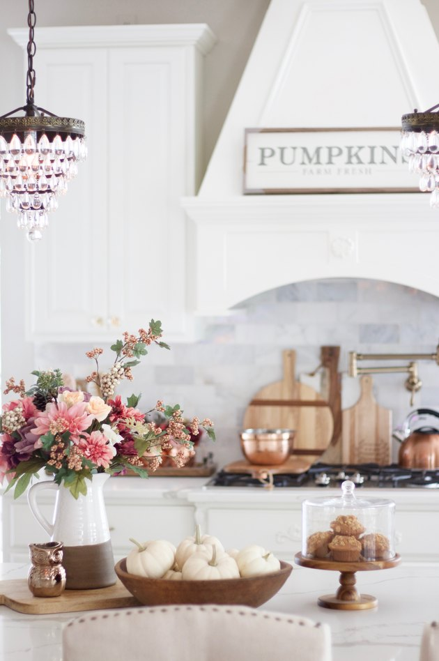 fall kitchen decor in white kitchen with flowers in a pitcher and pumpkins in a bowl