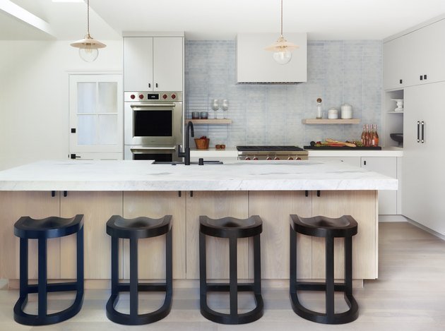 Modern coastal kitchen ideas with black bar stools and wood and marble island