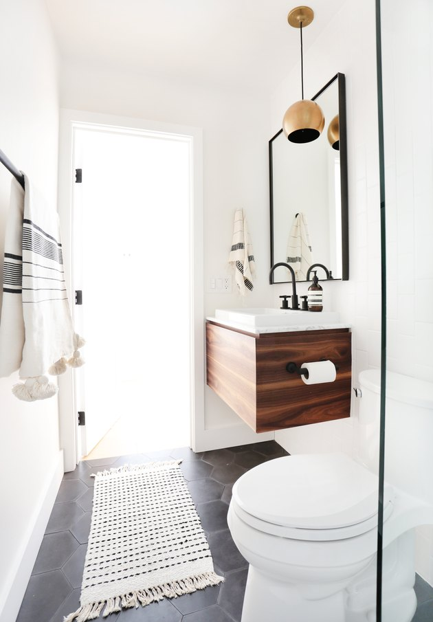 midcentury bathroom lighting idea with brass pendant hanging above floating vanity cabinet