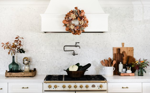 fall kitchen decor in white kitchen with wreath hanging on hood