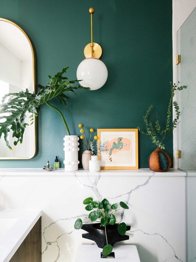 midcentury bathroom lighting idea with wall sconces on green walls and marble backsplash