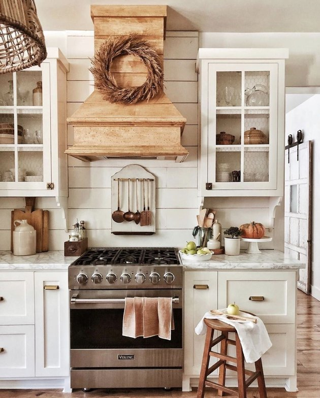 fall kitchen decor in white kitchen with stool and wreath on stove range