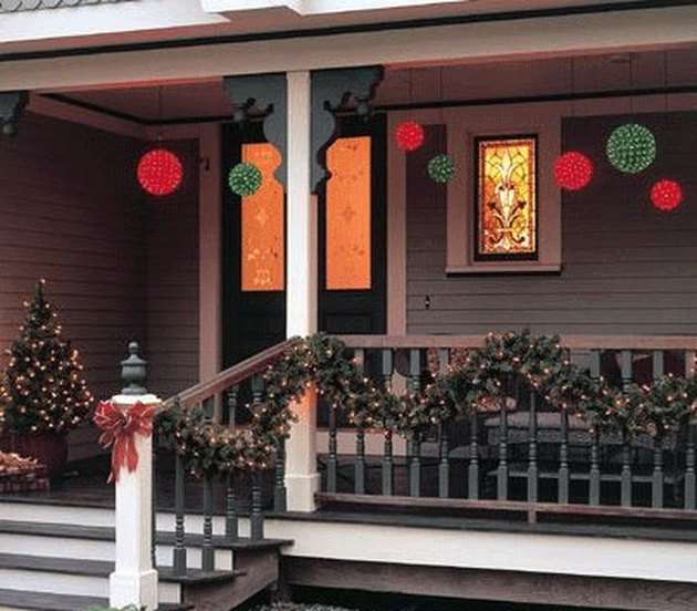 exterior Christmas decorations with Christmas garland and small Christmas tree lit with lights on front porch with red and green globe lights.