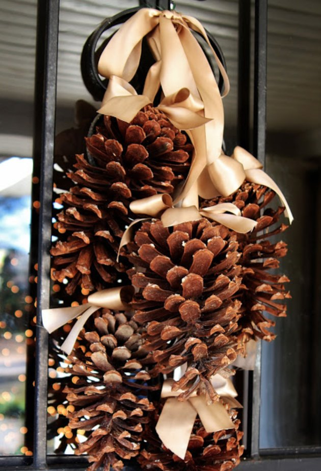 Christmas Door Decorations with Pinecones hung with beige satin ribbon.