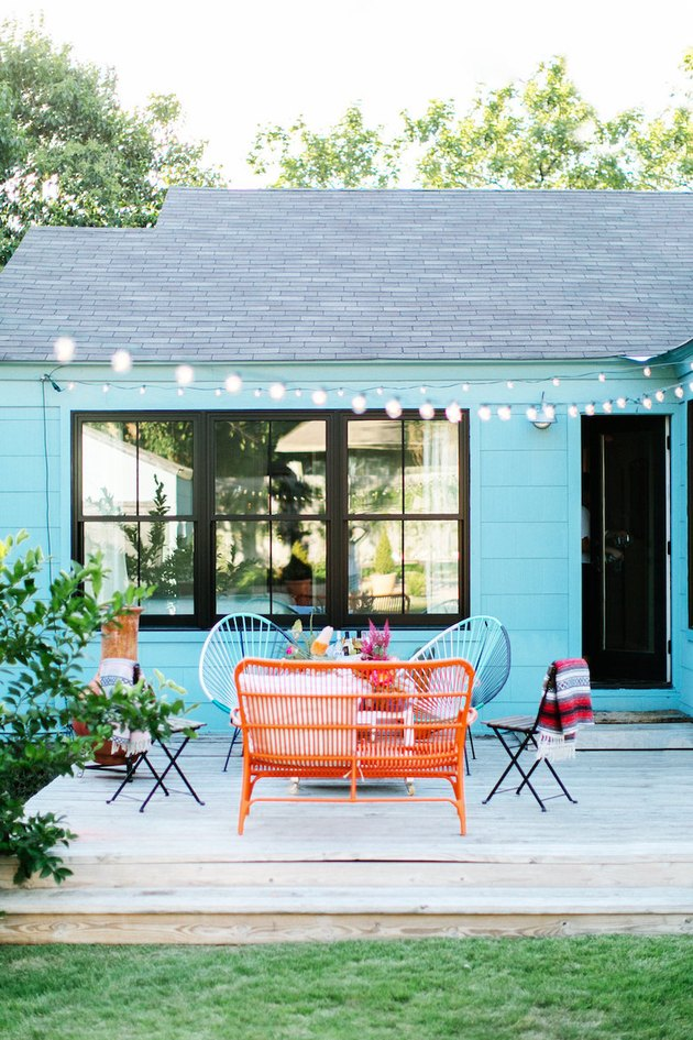 Turquoise blue exterior beach house colors with string lights and outdoor sitting area