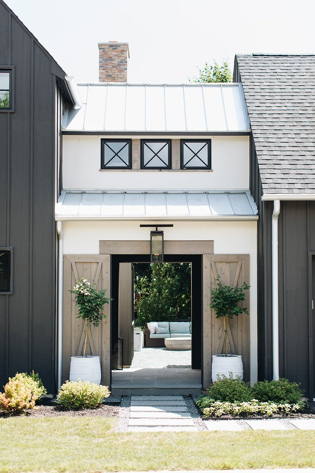 white and black exterior modern farmhouse with sliding barn doors