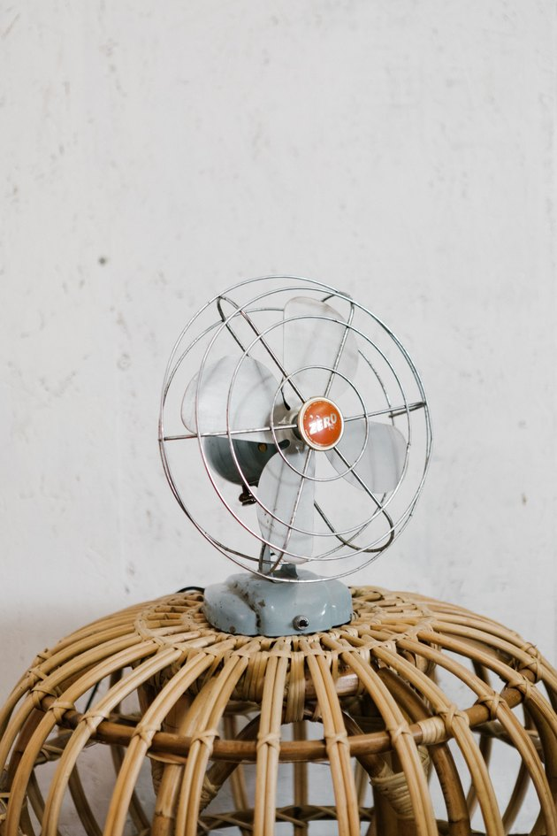 Small oscillating fan on rattan side table