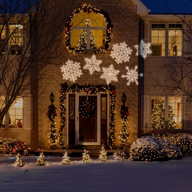 exterior Christmas decorations with Traditional Christmas decor on front of home with projection snowflake lights.