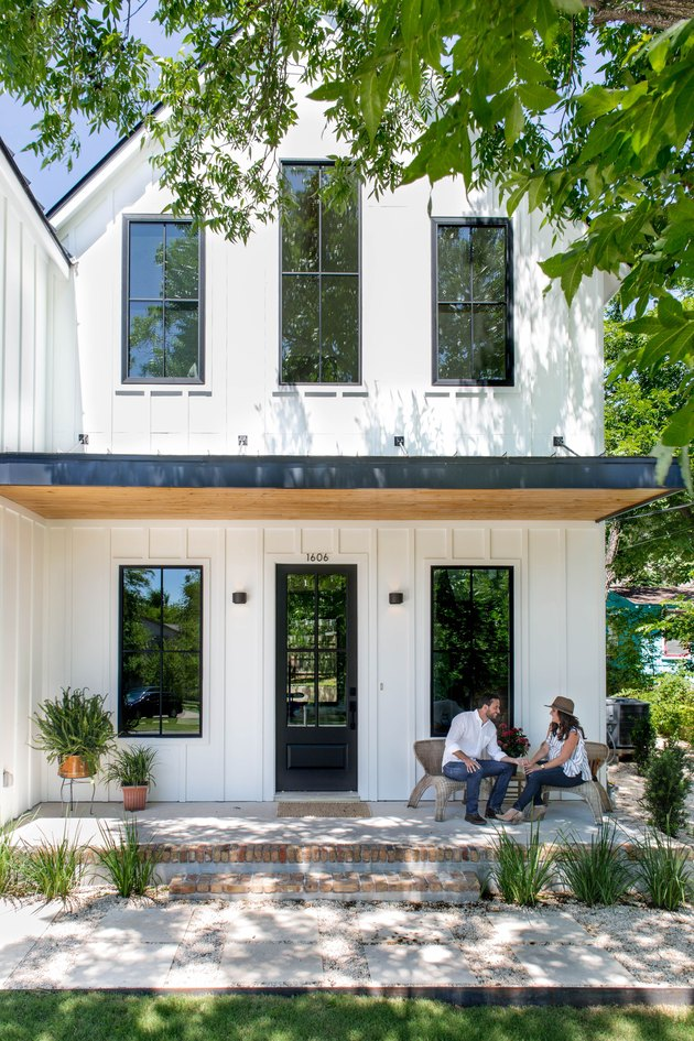 white exterior modern farmhouse with couple sitting on the porch