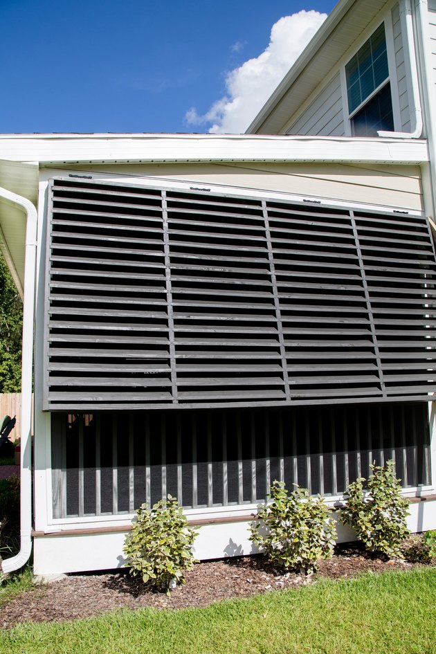 Black Bahama  exterior shutter style on traditional home alongside landscaping