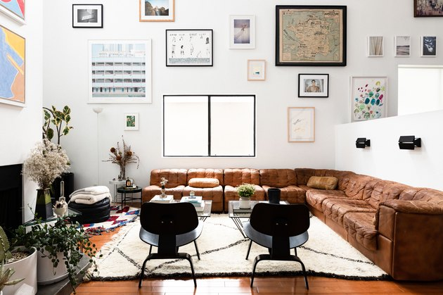 Living room with brown leather couch and high ceilings