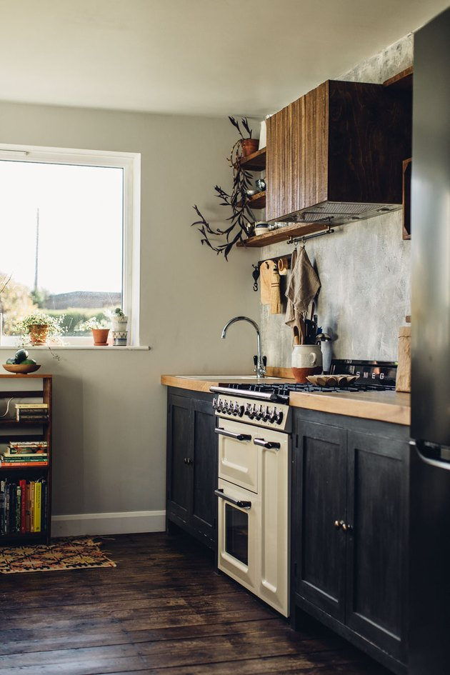 rustic kitchen with white retro stove and dark cabinets