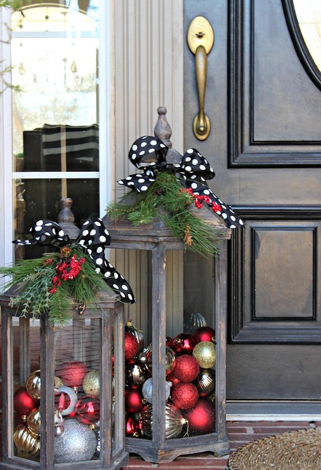exterior Christmas decorations with Distressed lanterns filled with holiday ornaments, greenery, polkadot ribbons, black front door.