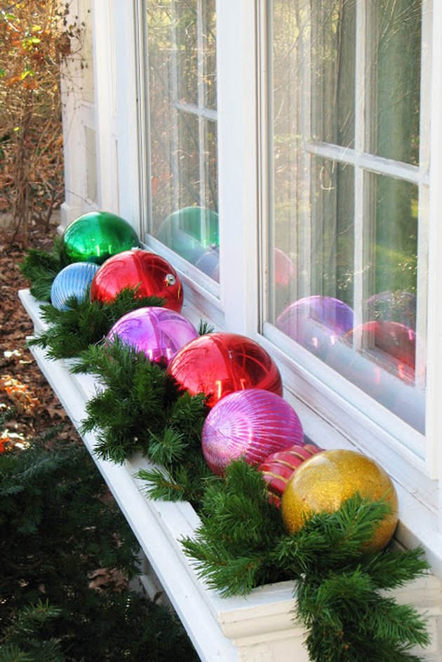 exterior Christmas decorations with Multi-colored Christmas ball ornaments and artificial greenery inside window box.