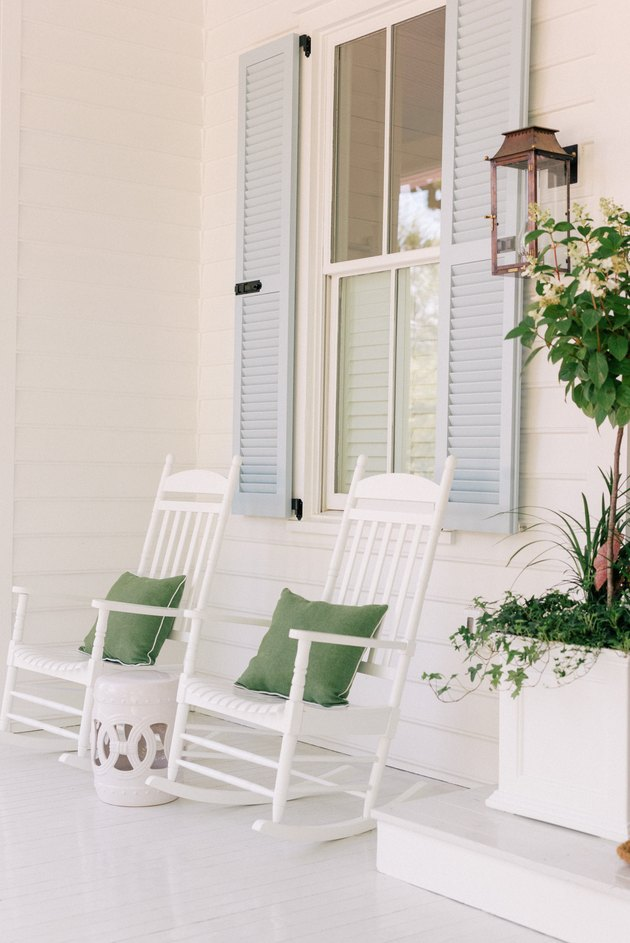 Light blue louvered exterior shutter style on white home alongside white rocking chairs