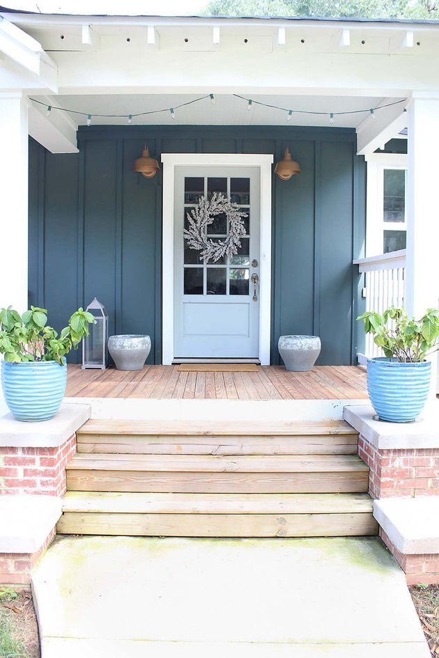 Teal green exterior house paint with farmhouse decor and brass barn lights