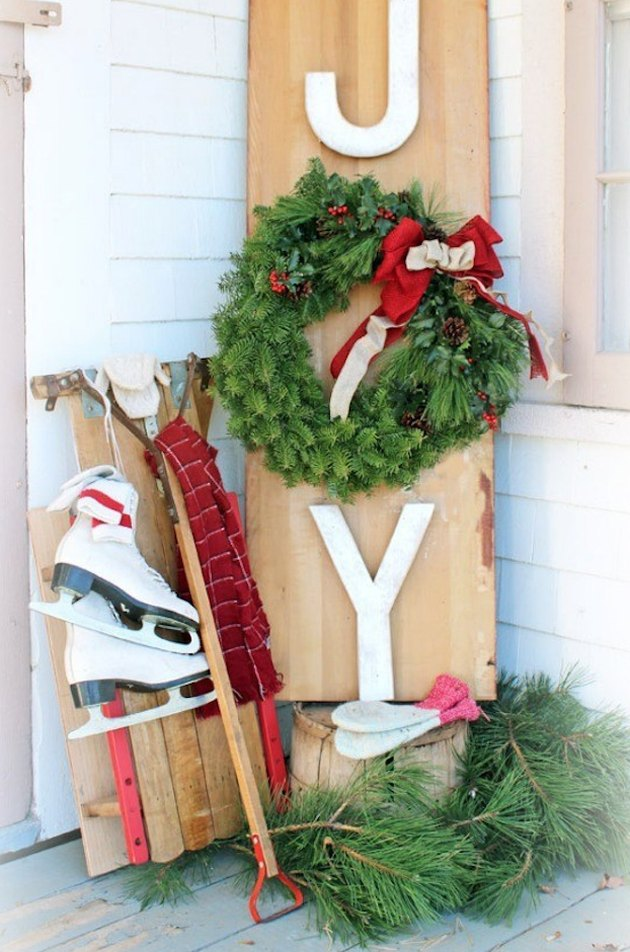 exterior Christmas decorations with DIY Joy sign with wreath, ice skates, sled, greenery.