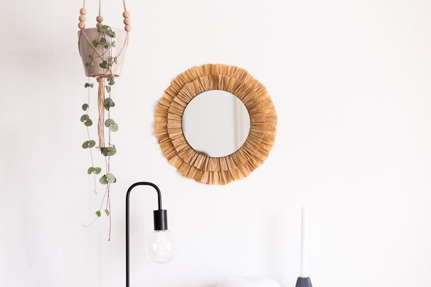 Raffia mirror on wall next to hanging plant.