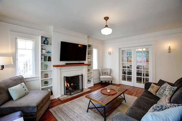 White and wood living room with built-in bookshelves.