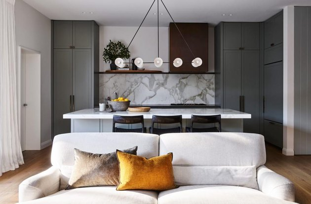 kitchen island lighting idea with ten light chandelier and marble backsplash