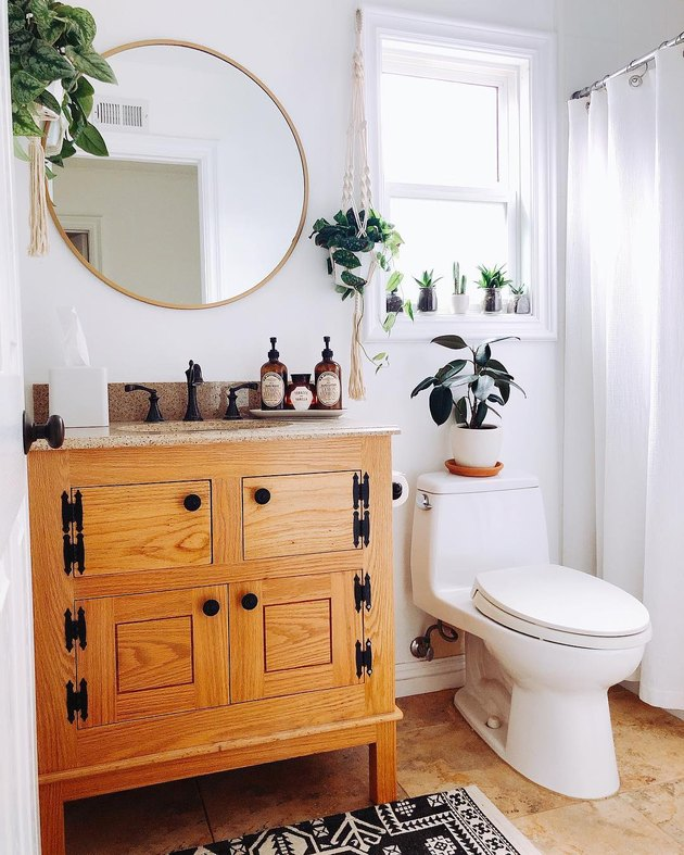 Bathroom with potted plants in windowsill above toilet