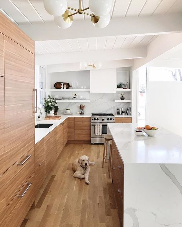 midcentury kitchen lighting idea with wood cabinets ant marble backsplash and countertops