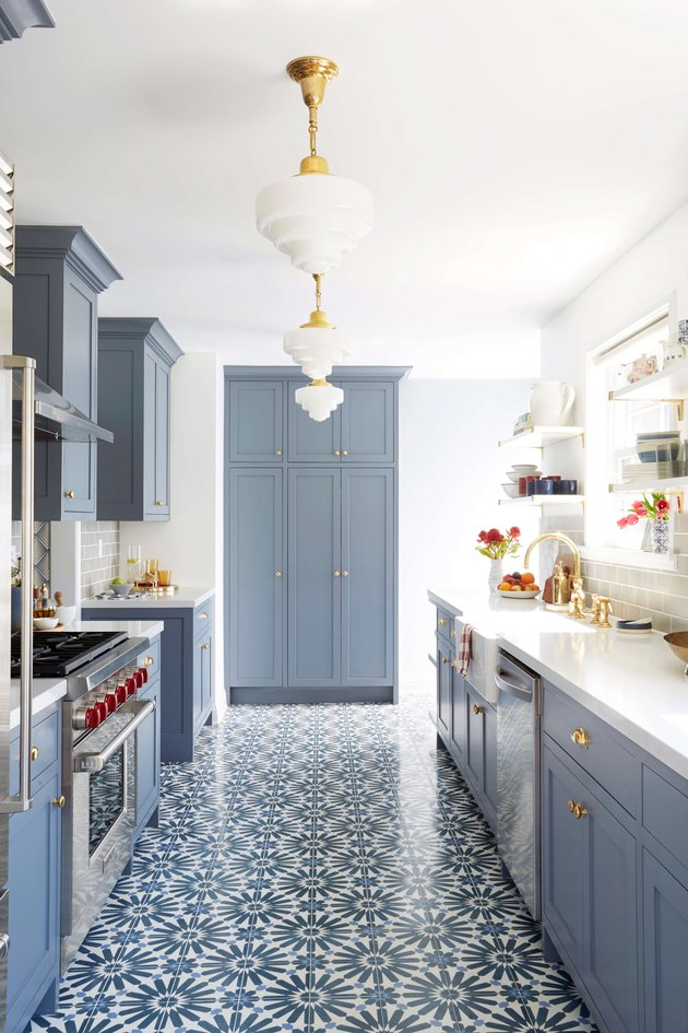 Blue patterned cement kitchen floor tile with blue cabinets and white countertops