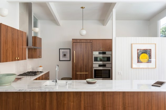midcentury kitchen lighting idea with circular pendant and wall sconces