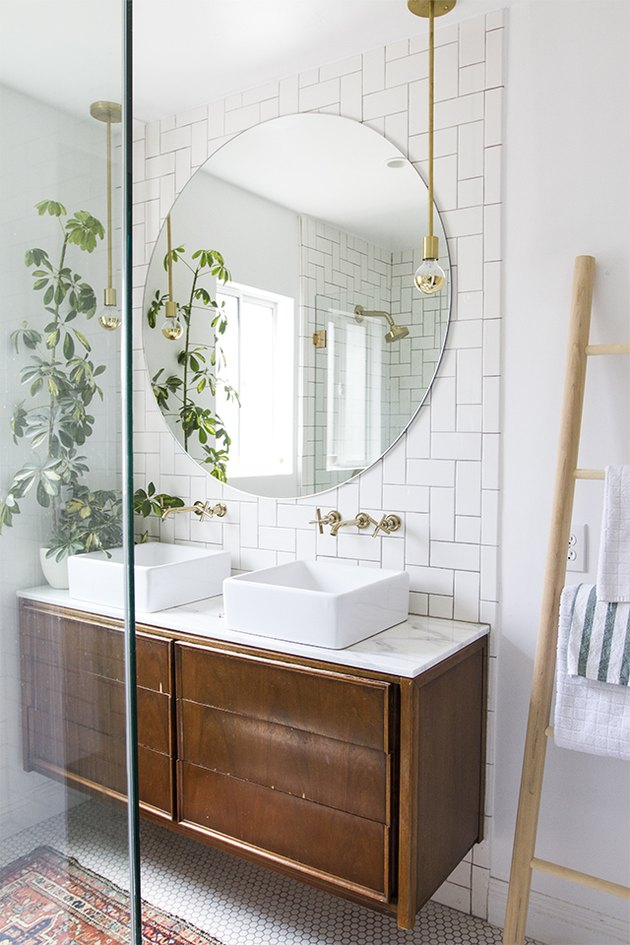 bathroom with white tile backsplash and vessel sinks ant potted plant on floating vanity
