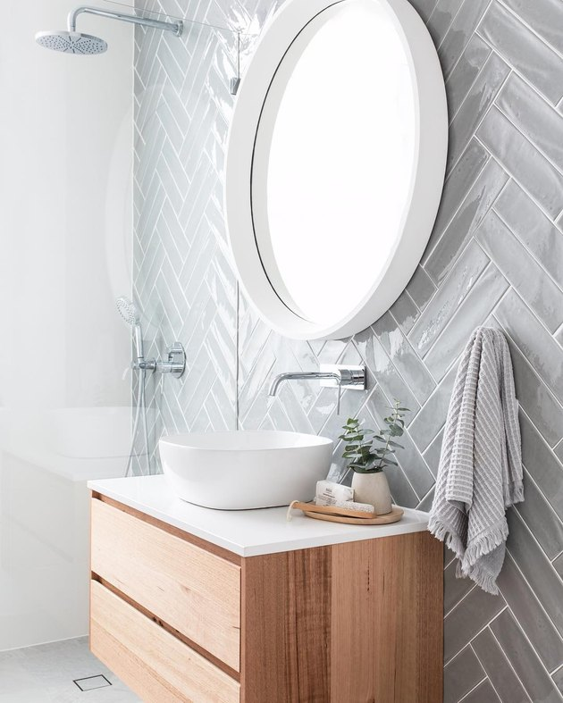 vessel bathroom sink with herringbone tile backsplash and round mirror