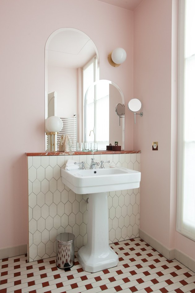 pedestal bathroom sink with pink walls and patterned floor tile