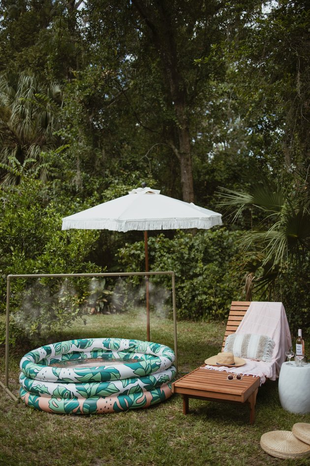 Green PVC pipe water mister over an inflatable pool next to lounge chair and fringe patio umbrella