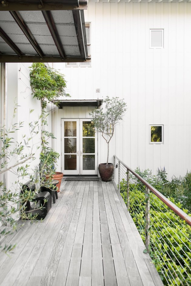 white home exterior with gray deck and modern railing
