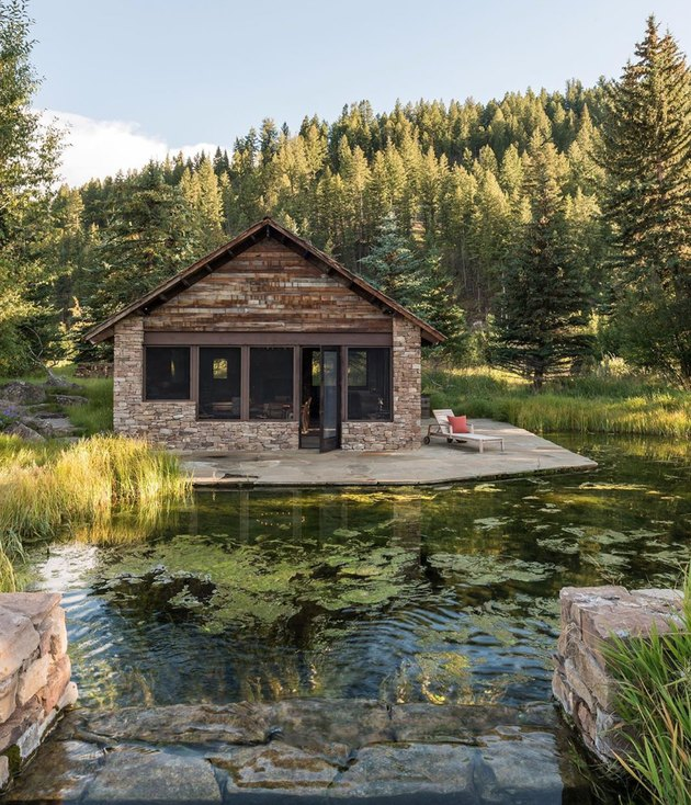 stone and wood modern cabin surrounded by water and trees