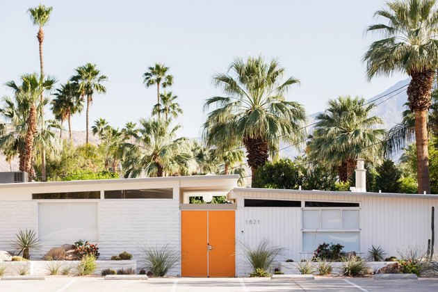 white home exterior on midcentury Palm Springs house with orange door surrounded by palm trees