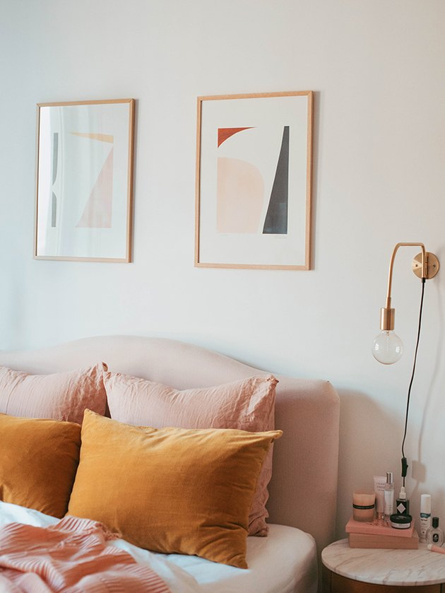 modern pink and orange bedroom with brass wall sconce
