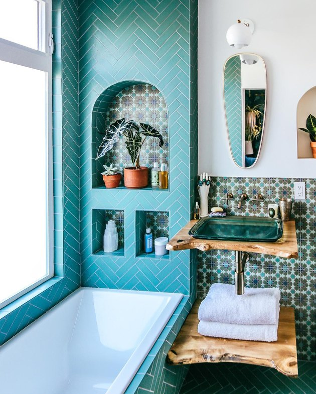 glass bathroom sink with patterned tile and wood countertop