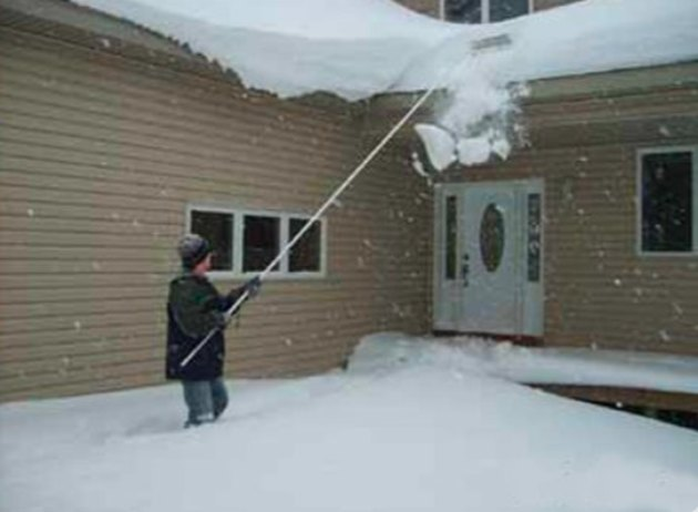 Raking snow from the roof.