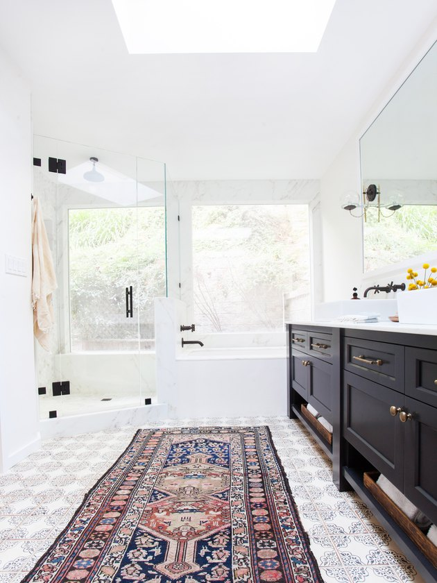 white bathroom with black vanity cabinet and area rug on patterned tile