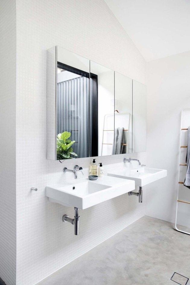 A pair of white wall-mounted bathroom sinks in a modern space with concrete flooring
